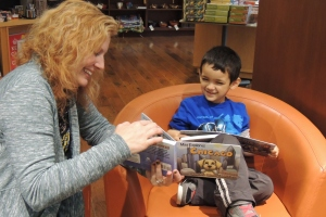 "When Reji has book signings and events, she makes sure each child gets some one-on-one reading time with her. She and this young boy from Chicago enjoyed ""Max Explores Chicago"" together at Barbara's Bestsellers in December 2014."